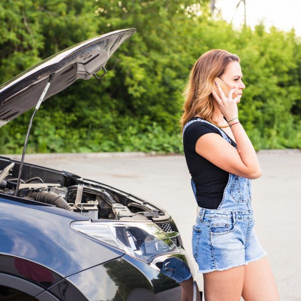young woman with broken down car with hood open call for help